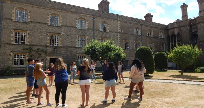 Students admire the architecture of Jesus College from afar