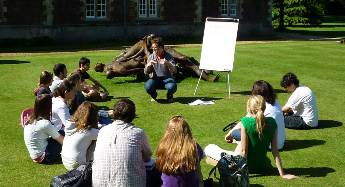 Students sit in a circle near Jesus college for their summer lecture