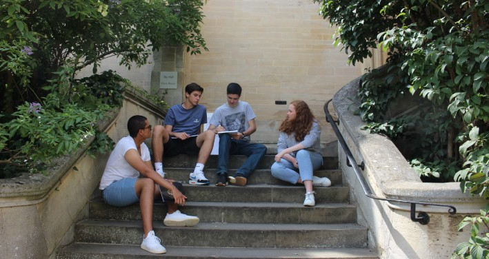 Students reading for their summer course on Pembroke College steps