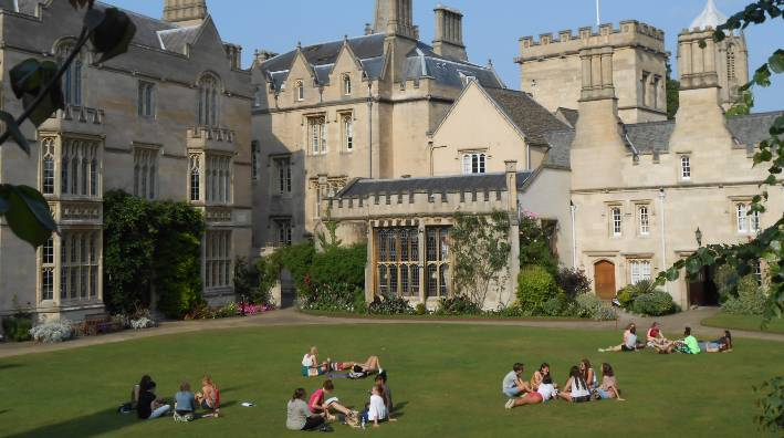 Students on grassy grounds of Pembroke College, Oxford
