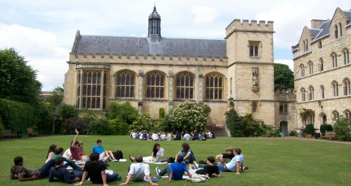 Students in a circle on the grass of Pembroke College at Oxford