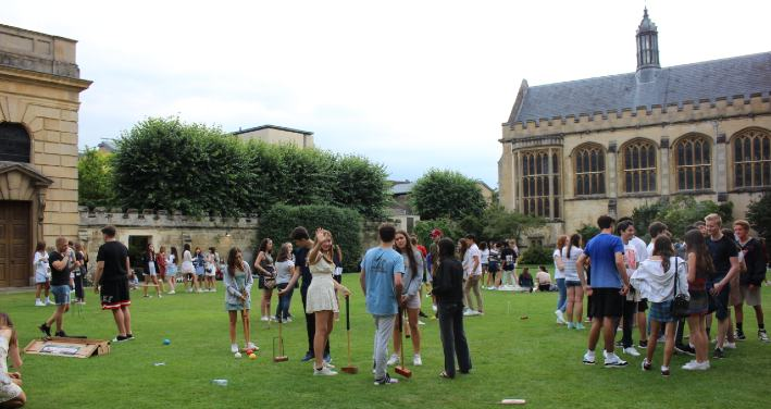 Students play croquet on grassy fields of Pembroke College in Oxford