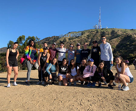 Students grouped in front of the Hollywood sign